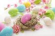 easter eggs in bird's nest and cherry blossom flowers on white background