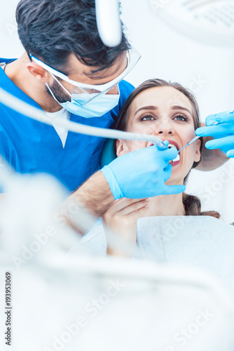 Fototapeta Beautiful young woman looking up relaxed during a painless dental procedure, done by her reliable dentist in a modern clinic with sterile equipment