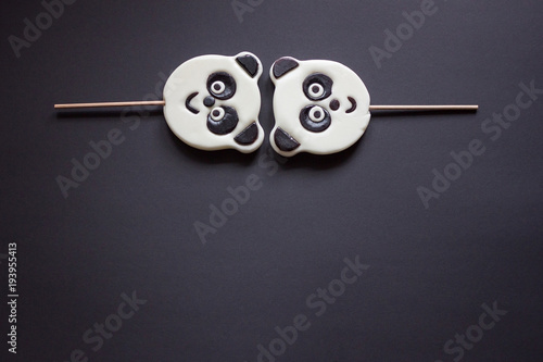 Plexiglas Panda 2 candies in the shape of a panda lies on top on a black background. Copy spase
