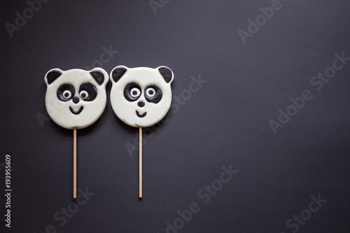 Fotobehang Panda Close up 2 lollipops in the form of an panda lies beside on a black background. Copy spase