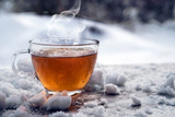 steaming hot tea in a glass cup is standing outside on a cold winter day with snow, copy space - 193967884