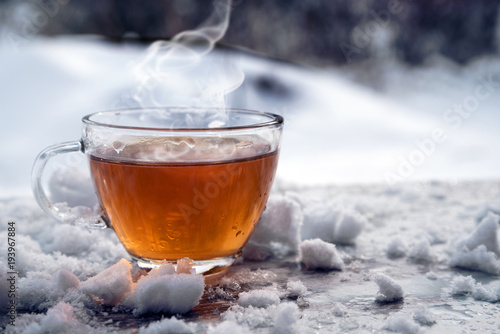 Papiers peints The steaming hot tea in a glass cup is standing outside on a cold winter day with snow, copy space