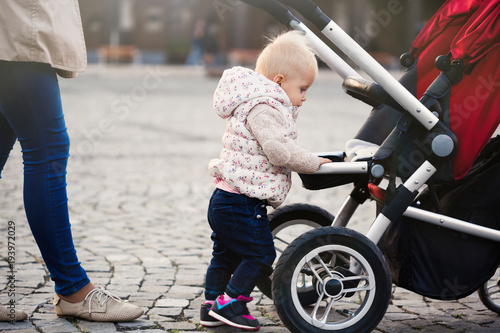 Beautiful toddler girl playing with his stroller walking outdoors