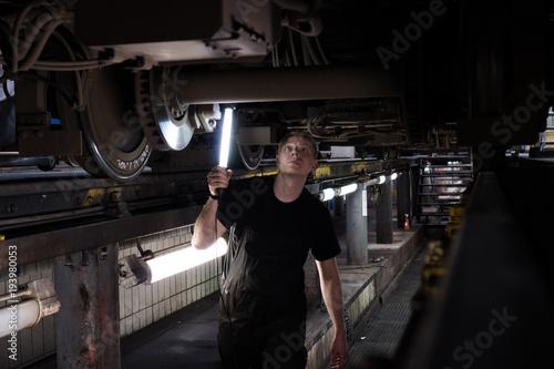 Fototapeta Mechanic using light to inspect a subway car