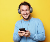 young man wearing headphones and holding mobile phone - 193981682