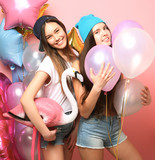 Two pretty emotional girls hold balloons and posing against pin - 193982472