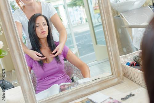 Fotobehang Kapsalon Hairdresser indicating to customer the length to cut her hair
