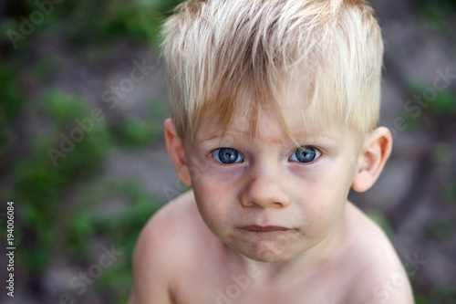 Portrait of a boy with blue eyes, a homeless child, a war child Poster