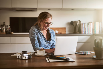 Smiling female entrepreneur working from home with a laptop