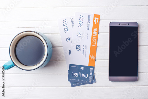 Cup of coffee train tickets and phone on white wooden background. Concept of buying the online ticket booking