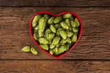 Beer brewing ingredients Hop cones in red heart bowl on wooden background. Beer brewery concept. - 194011846