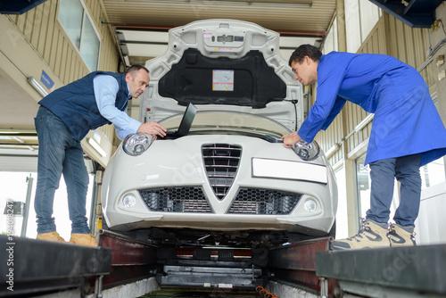 dwóch profesjonalnych mechaników sprawdzających silnik samochodu w garażu