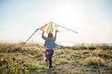 little boy run across the field with a kite in his hands trying to fly - 194024427