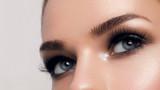Macro shot of woman's beautiful eye with extremely long eyelashes. Sexy view, sensual look. Female eye with long eyelashes - 194025832