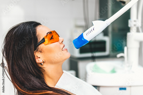 Teeth whitening in dental clinic for pretty female patient - 194027055