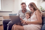 Happy caucasian family with laptop on sofa. - 194043402