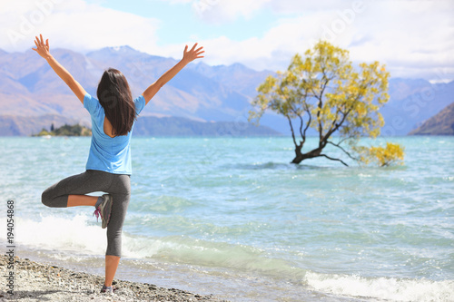 Fototapeta New Zealand morning yoga girl doing tree pose variation doing yoga practice with open arms at Wanaka lake by the lone tree, tourist travel popular attraction in New Zealand. Beach nature landscape.