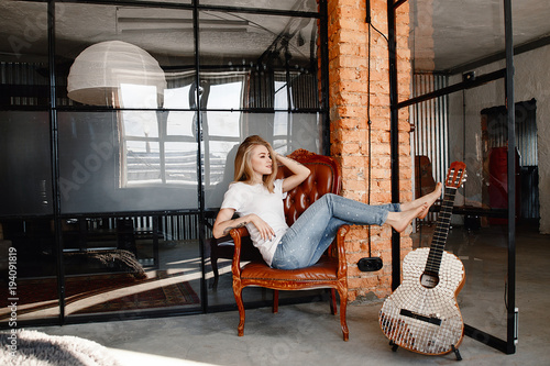 portrait-of-the-stylish-young-woman-of-the-blonde-in-a-white-t-shirt-and-jeans-in-an-interior-in-style-the-loft-the-girl-with-a-guitar