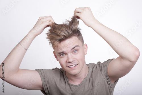 Fotobehang Kapsalon Jungem Mann stehen die Haare zu Berge, weil er sich in einer brenzlichen Situation befindet