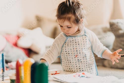 Fotobehang Kapsalon toddler girl in drawing apron draws fingers at home