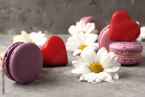 Aluminium Macarons Flowers, colorful macarons, heart shaped cookies, gift box on grey background. Close-up.