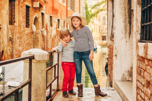 Fototapeta Two kids playing on the bridge in Venice. Little girl and boy visiting Venice, Italy. Small tourists in Europe