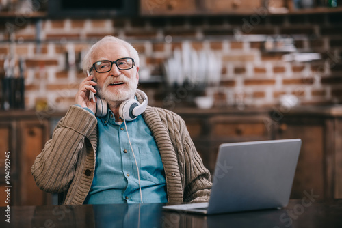 old-man-in-headphones-talking-on-phone-by-laptop
