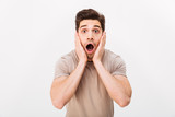 Horizontal portrait of scared man grabbing his face and screaming in stress, isolated over white background - 194102209
