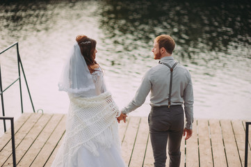 stylish bride and groom posing on the background of the river