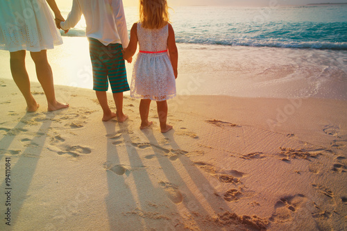Mother with son and daughter walk on sand beach