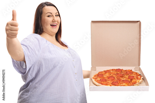 Overweight woman holding a pizza box and making a thumb up sign