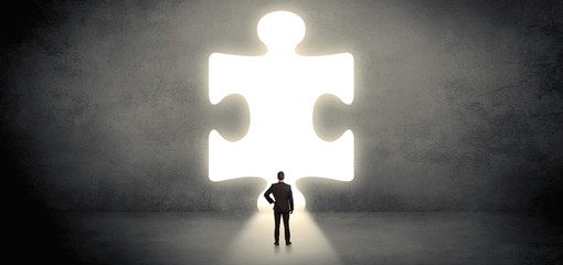 Businessman standing in front of a big puzzle piece