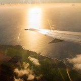 Last sunrays over Indian ocean. Romantic sunset on Reunion Island coast near Saint Denis from airliner. - 194164079