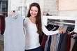 Portrait of cheerful woman choosing sweater