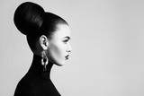 Retro style black and white fashion portrait of elegant female model with hair bun hairstyle and eyeliner makeup