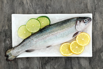 Rainbow trout health food on crushed ice with lemon and lime fruit on marble background. Very high in omega 3 fatty acid and beneficial to maintain a healthy heart. © marilyn barbone