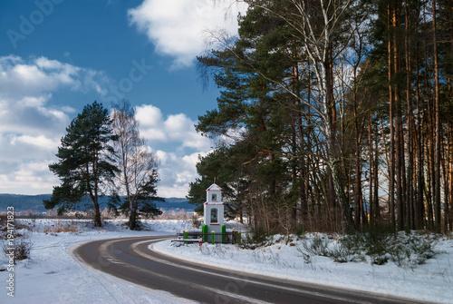 Tuinposter Weg in bos Przydrożna kapliczka na skraju lasu w zimowej szacie oświetlone porannym słońcem z niebieskim niebem z chmurami