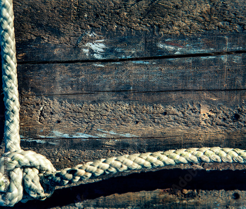 Aluminium Schip marine rope on weathered old wood background.