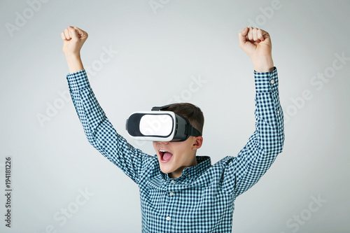 Young boy in virtual reality goggles on grey background