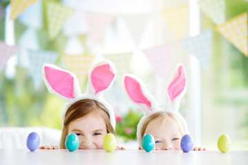 Two cute little sisters wearing bunny ears playing egg hunt on Easter