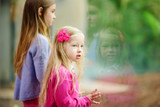 Cute little girl watching animals at the zoo on warm and sunny summer day. Child watching zoo animals through the window. - 194182239