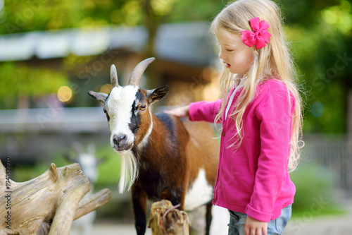 Wall mural Cute little girl petting and feeding a goat at petting zoo. Child playing with a farm animal on sunny summer day.