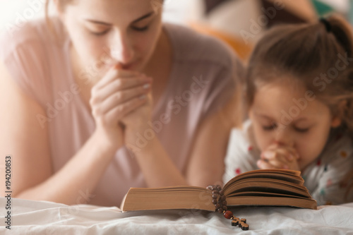 Religious Christian girl and her mother praying over Bible indoors