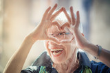Cute senior old woman making a heart shape with her hands and fingers - 194205689