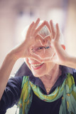 Cute senior old woman making a heart shape with her hands and fingers - 194205690