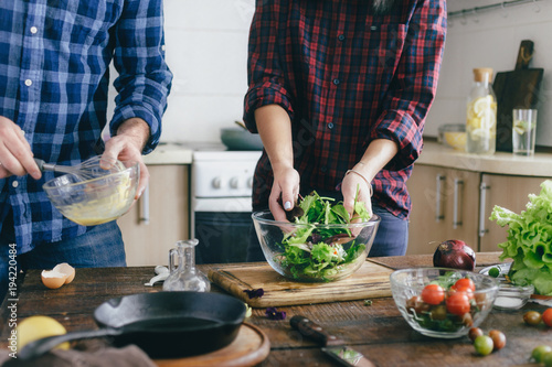 Couple preparing summer salad at home in the kitchen. Healthy food concept