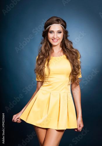 Fotobehang Kapsalon Beautiful girl model in a yellow dress on a blue background in the studio