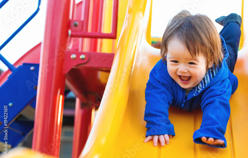 Happy toddler boy playing on a slide at a playground