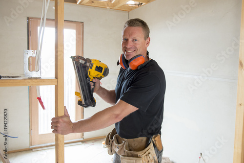 attractive and confident constructor carpenter or builder man working wood with electric drill at industrial construction site