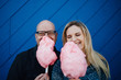 A man and a woman smiling and holding sticky, pink cotton candy infront of a blue wall